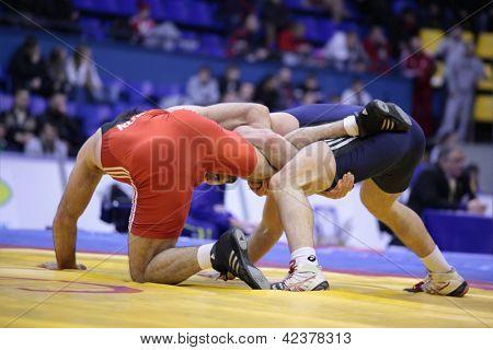 KIEV, UKRAINE - FEBRUARY 16: Match between Zubairov, Russia, red, and Turgaev, Kazakhstan during International freestyle wrestling and female wrestling tournament in Kiev, Ukraine on February 16, 2013