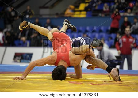 KIEV, UKRAINE - FEBRUARY 16: Match between Iakobishvili, Georgia, red and Kabisov, Russia during International freestyle wrestling and female wrestling tournament in Kiev, Ukraine on February 16, 2013