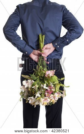 Man hold bouquet of flowers behind his back.  isolated on white