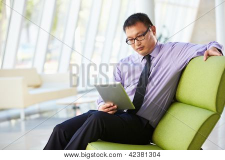 Businessman Sitting In Modern Office Using Digital Tablet