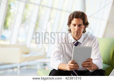 Businessman Sitting On Sofa In Office Using Digital Tablet