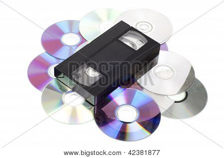 CD vs VHS. VHS cassette lay on the many CD disks isolated on whi