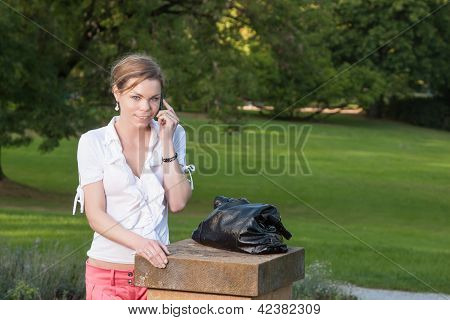 Woman With Smart Phone In The Park