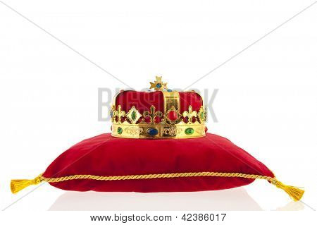 Golden crown on red velvet pillow for coronation