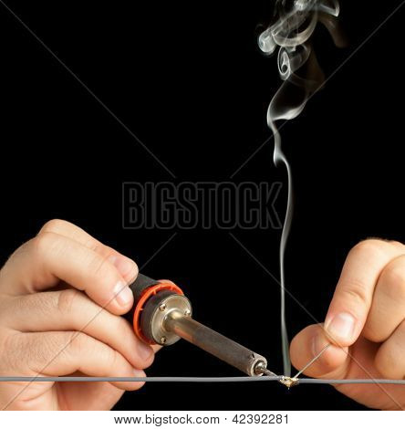 Technician soldering two wires together on a black background.