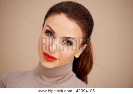 Gorgeous beautiful brunette with her hair tied back in a ponytail wearing a poloneck and red lipstick  studio headshot on a beige background