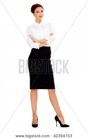 Beautiful businesswoman or corporate executive standing with folded arms looking at the camera  full length studio portrait isolated on white