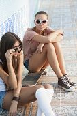 picture of roller-derby  - Two young skateboarding and roller skating girl friends sitting in empty swimming pool outdoors - JPG