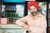 stock photo of rajasthani  - Portrait of Indian sikh man seller in turban with bushy beard at shop - JPG
