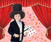 Young magician doing a card trick in a theater
