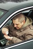 stock photo of overdose  - Man sitting in car with drugs in the hands - JPG