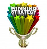 picture of cunning  - The words Winning Strategy bursting from a golden trophy surrounded by stars and fireworks to celebrate a good plan or management style that leads a team or group to victory - JPG