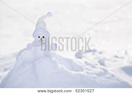 Little white snowman near snowbank.