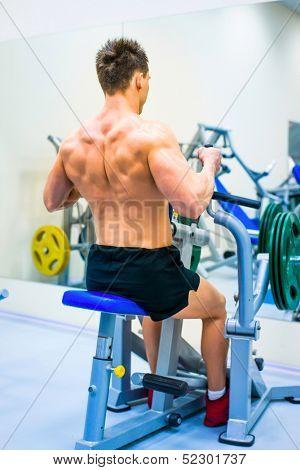 bodybuilder doing exercises on the simulator
