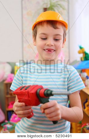 Boy In Plastic Helmet With Toy Drill