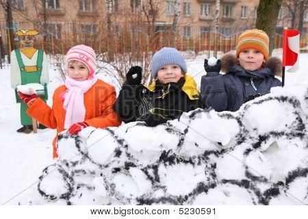 drei Kinder an Wand des Schneefestung in Hof