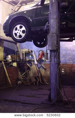 Car On Lift In  Workshop