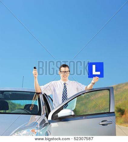 Happy man posing near his car, holding a L sign and car key after having his driver's licence on an open road, shot with a tilt and shift lens