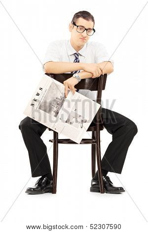 Disappointed young businessperson sitting on a wooden chair and holding a newspaper isolated against white background