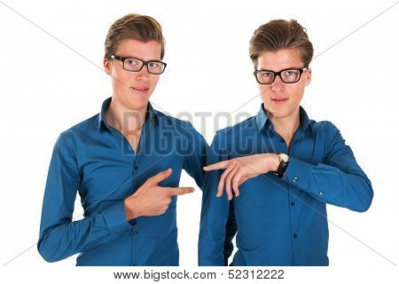 Identically adult male twins pointing to each other in studio