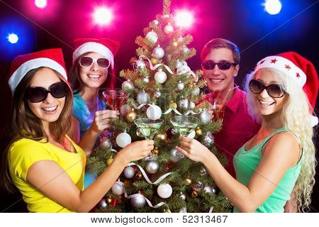 Happy people clinking by glases around the Christmas tree