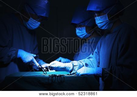 Team of surgeons holding surgical equipment at the operating table and working