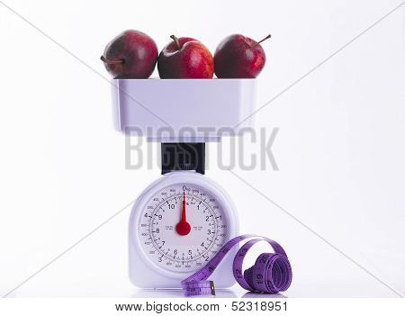Three Red Apples On Weighing Scales With Tape Measure
