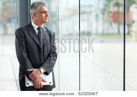 thoughtful mid age businessman looking through office window