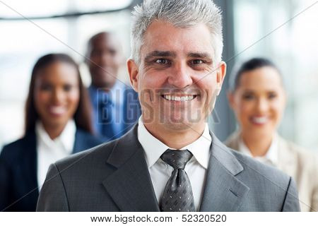 handsome senior businessman standing with co-workers on background