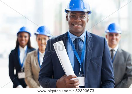 handsome african male architect holding blue print and team