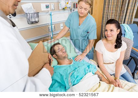Young woman looking at doctor while holding man's hand in hospital room
