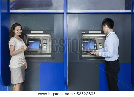 Two people standing and withdrawing money from ATM
