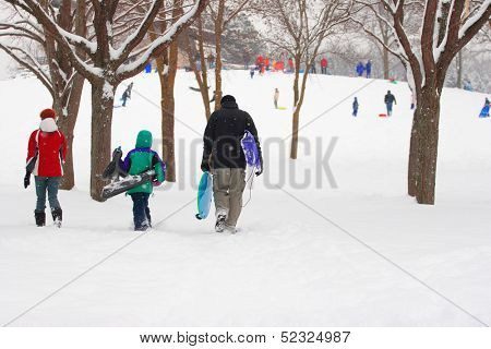 Family walking to the sledding hill