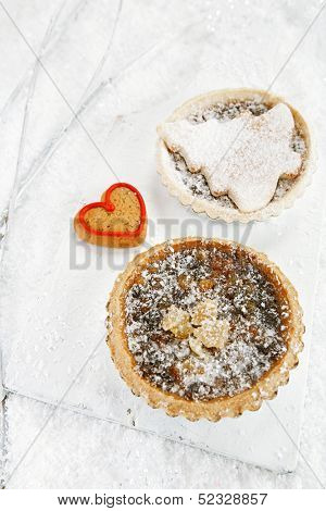 christmas  tart with mincemeat and tart with marzipan tree  on white snow festive background