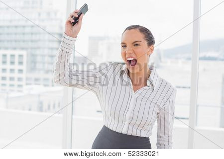 Offended businesswoman screaming and throwing her mobile phone while standing in her office