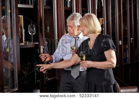Two seniors drinking glass of champagne at wine tasting event