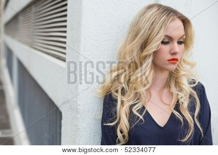 Pensive attractive blonde wearing classy dress outdoors against building