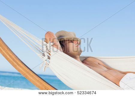 Man lying on hammock sleeping with straw hat on face on holidays