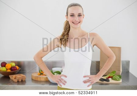 Pretty smiling woman standing hands on hips in bright kitchen
