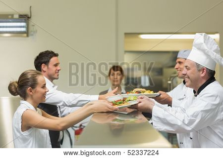 Two cooks handing plates to servers being watched by the female manager