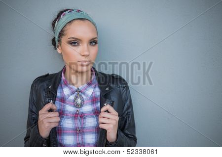 Beautiful woman with hairband posing and looking at camera against a grey wall