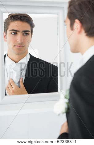 Serious young bridegroom straightening his tie looking in a mirror