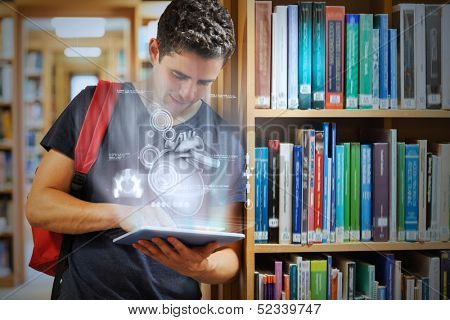 Handsome college student working on his digital tablet with futuristic interface in university library