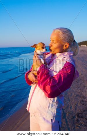 Young Woman With Her Dog On A Beach