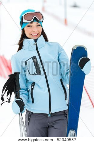 Half-length portrait of female wearing sports jacket and goggles who has skis in hands