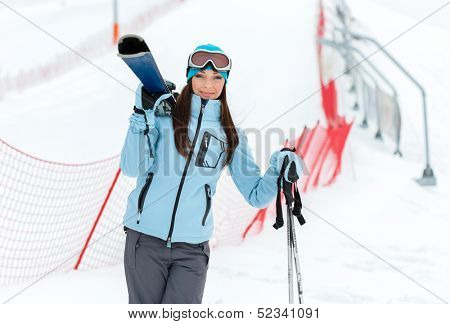 Half-length portrait of female wearing sports jacket and goggles who holds skis