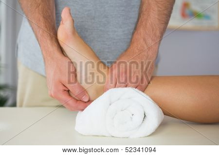 Physiotherapist checking patients foot on towel in bright office