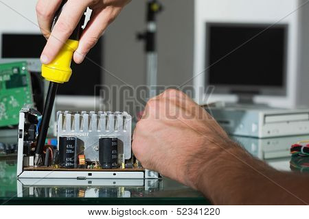 Computer engineer repairing hardware with screw driver in bright office