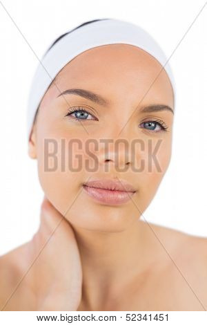 Attractive woman wearing hairband holding her neck against white background