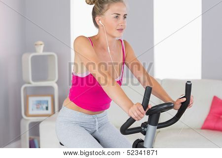 Sporty determined blonde training on exercise bike listening to music in bright living room